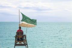 Salvavidas en la orilla del mar Playa guardada, atalaya con una bandera verde foto de archivo libre de regalías