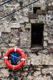 Salvavidas rojo en el embarcadero de piedra en playa srilanquesa Fotografía de archivo