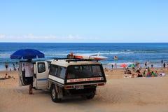 Salvavidas, vehículo y gente de la playa Imagenes de archivo