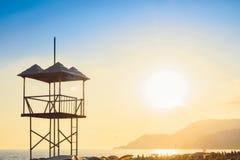 Salve o Sandy Beach do oceano do mar da torre da salva-vidas no por do sol na noite Fotos de Stock