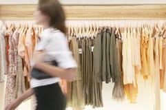 Salve recorrer auxiliar colgando la ropa en tienda Imagen de archivo libre de regalías