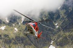 Salvi l'elicottero che decolla in tetra montagne nuvolose in slovacco immagini stock libere da diritti