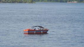 Salvi la barca rossa sull'acqua davanti alla spiaggia archivi video