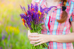 Salvia. Girl holds bouquet of salvia and camomile royalty free stock images