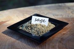 Salvia sfregata in un piccolo piatto nero con l'etichetta Immagini Stock Libere da Diritti