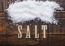 Salz auf hölzernem Brett des Schmutzes mit Buchstaben unten Lizenzfreies Stockfoto
