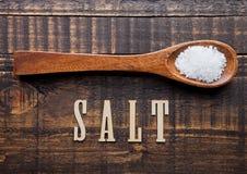 Salz auf hölzernem Löffel mit Buchstaben unten Stockbilder