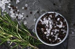 Salz, Pfeffer und Rosmarin auf schwarzem Marmor stockbilder