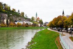 Salzach river in Salzburg, Austria. Bank of river with green grass and buildings. Autumn city landscape. Beautiful European city landscape Royalty Free Stock Photo