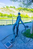 Salzburg, Áustria - 1º de maio de 2017: Estátua de bronze do Nude do ciclista de Radfahrer por Lotte Ranft ao lado da ponte de Ma foto de stock royalty free