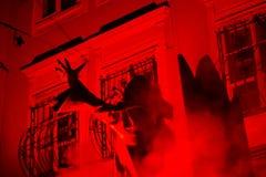 Salzburg, Áustria: 3 de dezembro de 2014: Krampus na posição assustador com sombra nas construções velhas da cidade de Salzburg e fotos de stock