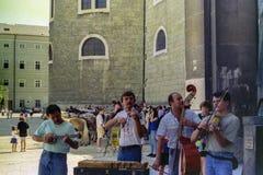 SALZBURG, ÁUSTRIA, 1988 - os músicos da rua mantem distraído turistas no quadrado principal de Salzburg foto de stock royalty free