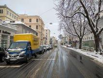 Salzburg, Áustria - trafique 13 de fevereiro de 2018 a estrada na neve da árvore do automóvel do carro de Europa da estação do in Fotografia de Stock Royalty Free
