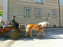 Salzburg Österrike - Maj 01, 2017: Centralt ställe i den Salzburg staden med vagnar och hästar Royaltyfri Foto