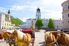 Salzburg Österrike - Maj 01, 2017: Centralt ställe i den Salzburg staden med vagnar och hästar Fotografering för Bildbyråer