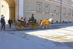 Salzburg Österrike - Maj 01, 2017: Centralt ställe i den Salzburg staden med vagnar och hästar Royaltyfri Fotografi