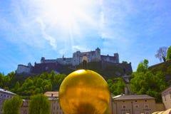 Salzburg Österrike - Maj 01, 2017: Den guld- bollstatyn med en man på den bästa skulpturen, Kapitelplatz fyrkant, Salzburg, Arkivfoto