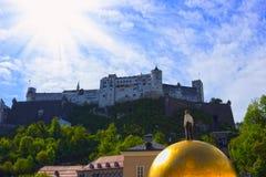 Salzburg Österrike - Maj 01, 2017: Den guld- bollstatyn med en man på den bästa skulpturen, Kapitelplatz fyrkant, Salzburg, Arkivfoton