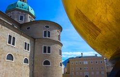 Salzburg Österrike - Maj 01, 2017: Den guld- bollstatyn med en man på den bästa skulpturen, Kapitelplatz fyrkant, Salzburg, Arkivbilder