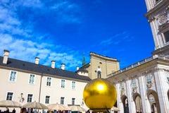 Salzburg Österrike - Maj 01, 2017: Den guld- bollstatyn med en man på den bästa skulpturen, Kapitelplatz fyrkant, Salzburg, Royaltyfri Foto