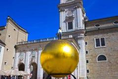 Salzburg Österrike - Maj 01, 2017: Den guld- bollstatyn med en man på den bästa skulpturen, Kapitelplatz fyrkant, Salzburg, Royaltyfri Bild