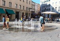 Salzburg Österrike: Ungdom och barn har gyckel med en springbrunn royaltyfri fotografi