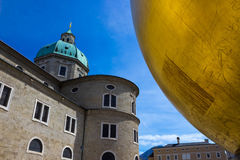 Salzburg, Austria - May 01, 2017: The golden ball statue with a man on the top sculpture, Kapitelplatz Square, Salzburg, Stock Photos
