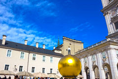 Salzburg, Austria - May 01, 2017: The golden ball statue with a man on the top sculpture, Kapitelplatz Square, Salzburg, Royalty Free Stock Photo