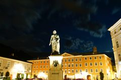 Statue Mozart in Square at night illuminated and golden in colo Stock Photos