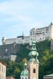 Salzburg Castle (Hohensalzburg) framed by church towers Stock Image