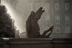 Salzburg, Residenzbrunnen, a old water spout fountain in the heart of the city, romantic backlight. Holiday or vacation in Austria, sightseeing in summer and Stock Photo