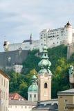 Salzburg slott som inramas av kyrkliga torn II Fotografering för Bildbyråer