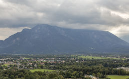 Salzburg suburb cityscape with beginnings of the Alps in clouds. Royalty Free Stock Photography