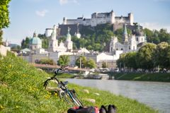 Free Salzburg Summer Time: Panoramic City Landscape With Salzach With Green Grass And Historic District. Bicycle In The Foreground Royalty Free Stock Photography - 162977637