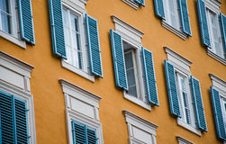 Salzburg Traditional Facade. Salzburg Austria Traditional Orange Facade with Old Windows and blue Wooden Blinds Royalty Free Stock Photography