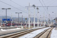 Salzburg train station tracks and lines. Salzburg train station tracks with electric lines and signal lights, snow between the tracks Stock Photo