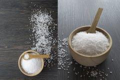 Salzen Sie Kristalle in einer hölzernen Schüssel mit Löffel Stockbilder