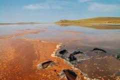 Salzen Sie Teich mit orange Flecken und blauem Himmel des freien Raumes Lizenzfreie Stockbilder