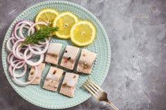 Salzheringe mit Scheiben der roten Zwiebel und der Zitrone Lizenzfreies Stockfoto