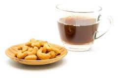 Salzige Acajounüsse in der hölzernen Platte und in einem Tasse Kaffee Lizenzfreie Stockfotos