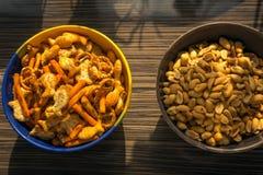 Salzige Snäcke und Erdnüsse in den Schüsseln Stockfoto