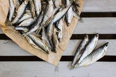 Salziger Trockenfisch auf dem braunen Papier Kleine Vorratfische stockbilder