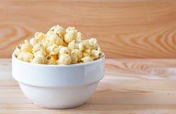 Salziges Popcorn der Luft Eine Schüssel Popcorn auf einem Holztisch lizenzfreie stockfotos