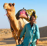 Camel man leads his camel across the Thar desert Royalty Free Stock Images