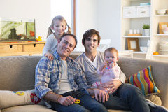 Sam sex couple at home with daughters. Same sex male couple smiling for the camera with their daughters at home Stock Photo
