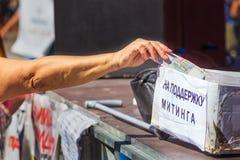 Samara, im August 2018: eine Hand, die Geld zur Nächstenliebe gibt lizenzfreies stockfoto
