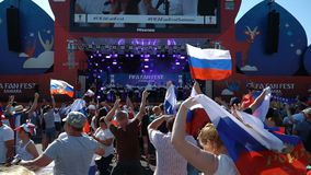 Football fans at the official FIFA FAN FEST zone. SAMARA - JUNE 25, 2018: Slow motion - football fans waving hands and flags, before the game Uruguay - Russia at stock footage