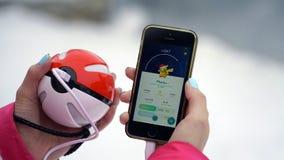 Samara, Rússia - 15 de dezembro de 2016: a mulher que joga o pokemon vai em seu iphone o pokemon vai jogo para múltiplos jogadore Fotografia de Stock Royalty Free