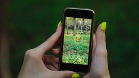 Samara, Rússia - 31 de julho de 2016: a mulher que joga o pokemon vai em seu iphone o pokemon vai jogo para múltiplos jogadores c video estoque