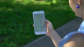 Samara, Rússia - 4 de julho de 2017: a mulher que joga o pokemon vai em seu iphone 6s mais o pokemon vai jogo para múltiplos joga video estoque